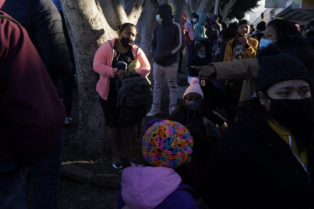 A woman seeking asylum in the United States waits with others for news of policy changes, Friday, Feb. 19, 2021, in Tijuana, Mexico. After waiting months and sometimes years in Mexico, people seeking asylum in the United States are being allowed into the country starting Friday as they wait for courts to decide on their cases, unwinding one of the Trump administration's signature immigration policies that President Joe Biden vowed to end. (AP Photo/Gregory Bull)