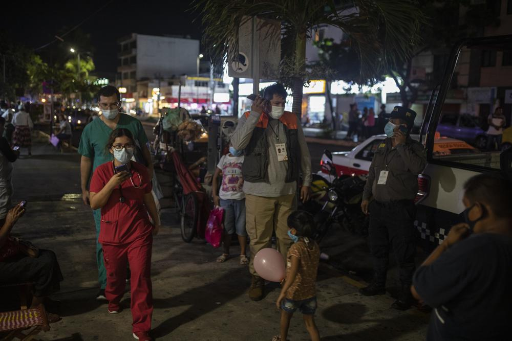 Health workers communicate on their mobile phones as they stand outside Veracruz General Hospital . Credit: AP
