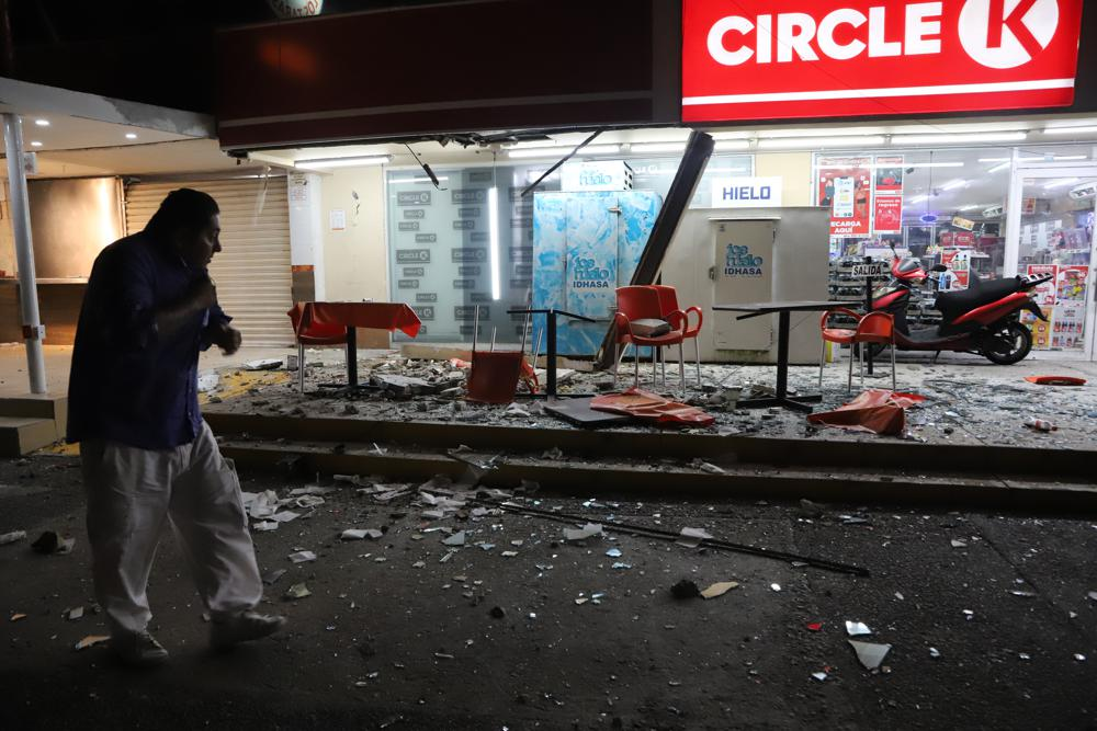 A man walks in from of a convenience store on a street covered with debris after a strong earthquake. Credit: AP